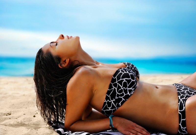 protezione solare bella donna sdraiata sulla spiaggia tipo scuro fototipo costume da bagno due pezzi nero mare estate