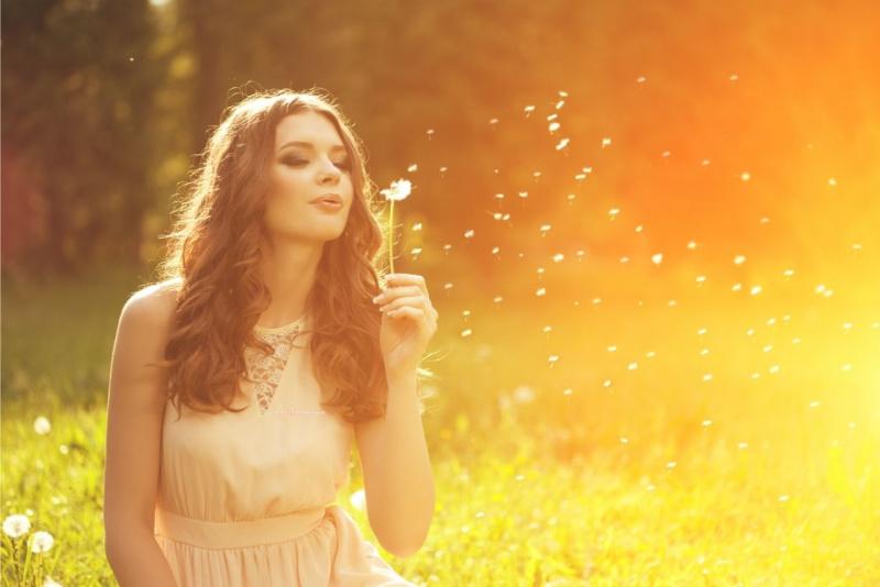 bella donna capelli lunghi soffia fiore soffione tarassaco tramonto prato dente di leone