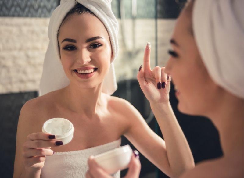 giovane bella donna applica crema viso davanti lo specchio bagno