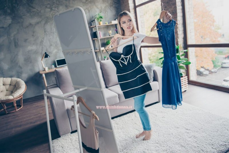 giovane donna sceglie abiti davanti lo specchio grucce jeans t-shirt bianca