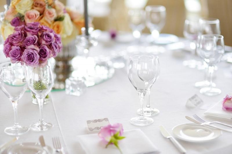 tavola apparecchiata a festa candele bouquet rose rosa arancione viola calici cristallo piatti ceramica bianca