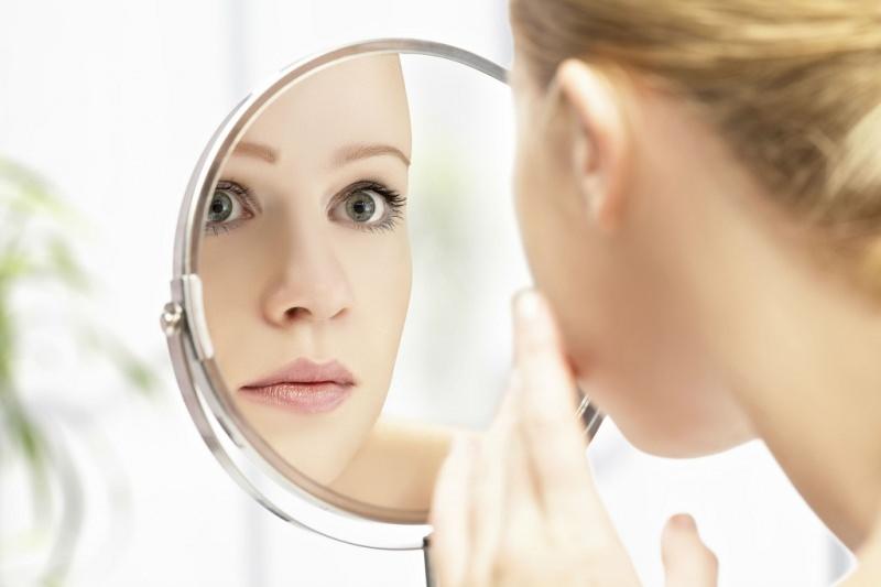 Piccole imperfezioni del viso: ecco come combatterle! bellezza viso donna allo specchio occhi azzurro verde labbra
