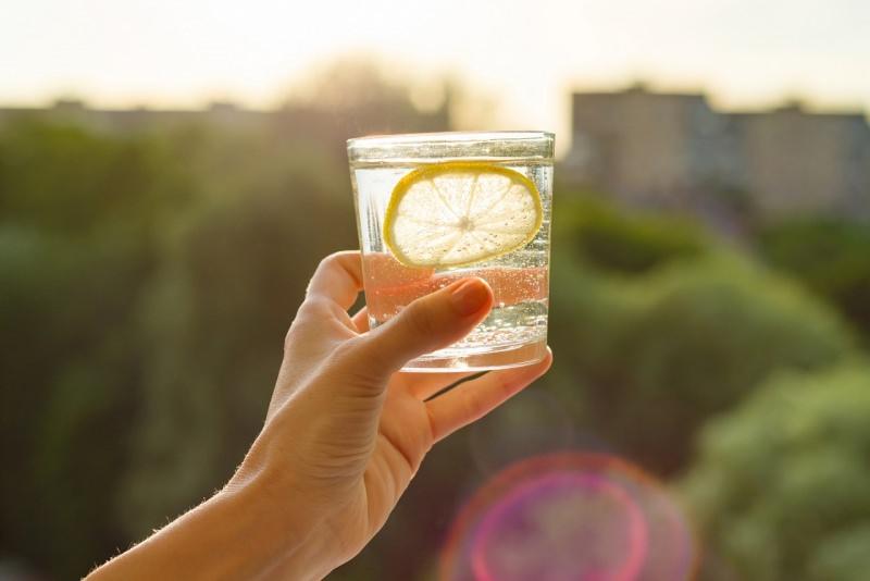 mano tiene bicchiere acqua e feta di limone natura