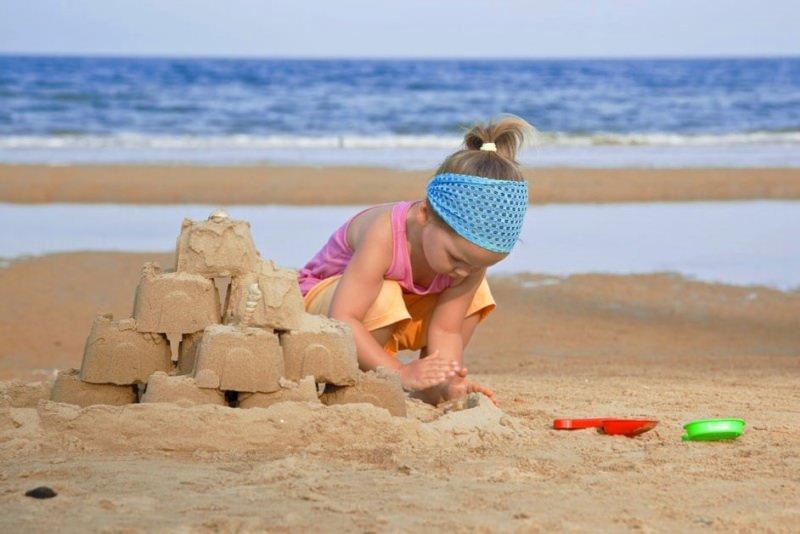 Attività da Fare al Mare con il Tuo Bambino bambina spiaggia castello di sabbia canottiera rosa pantalone bermuda arancione bandana rete azzurra paletta plastica rossa setaccio verde estate vacanza