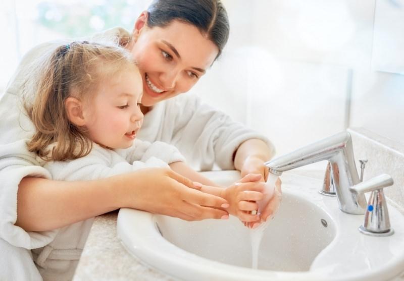 giovane donna mamma lava mani figlia bambina rubinetto bagno