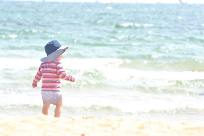 Attività da Fare al Mare con il Tuo Bambino bambina riva spiaggia battigia onde maglietta maniche lunghe righe rosa fucsia grigio cappello blu azzurro estate vacanze
