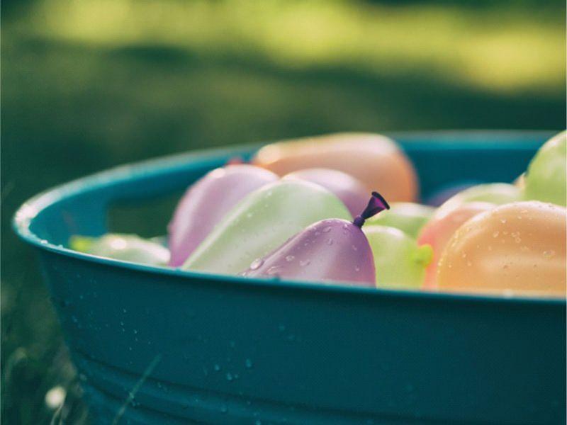 Attività da Fare al Mare con il Tuo Bambino giochi estate vacanza spiaggia patata bollente secchio grigio ghisa palloncini colorati viola verde arancione giallo rosa