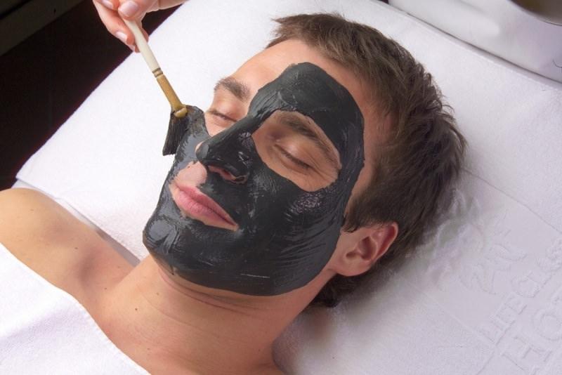 Come fare la Black Mask versione vegana viso uomo occhi chiusi capelli castani relax maschera nera applicata con pennello riposo lettino cuscino bianco mano donna