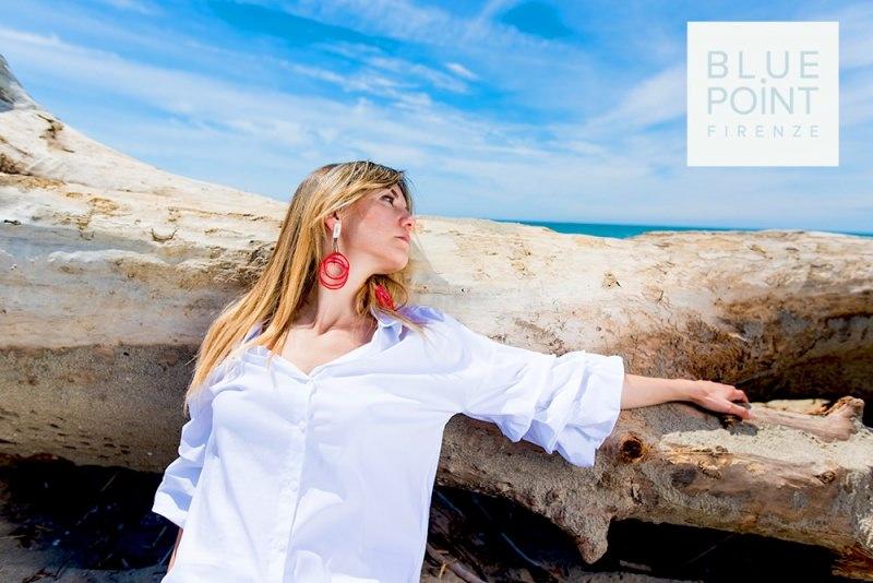 """Mini guida ai """"gioielli in vacanza"""" estate mare donna capelli lisci biondi moda bijoux orecchini cerchi rossi pendenti camicia bianca scoglio cielo azzurro nuvole"""