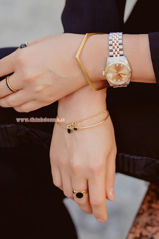donna con bracciali e orologio oro anelli sottili abito nero