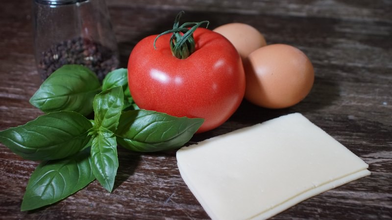 Conosci la dieta del pomodoro? Come perdere peso in pochi giorni colazione salata uova bicchiere pepe nero foglie basilico tavolo legno fette formaggio
