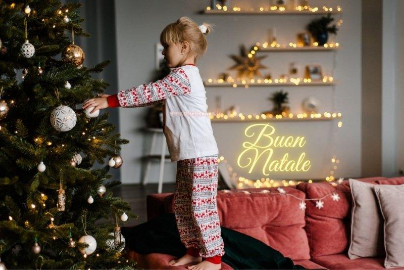 bambina decora albero di natale festa luci decorazioni natalizie oro divano palline