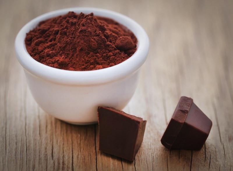 cacao amaro in polvere nella ciotola di ceramica bianca cioccolato fondente