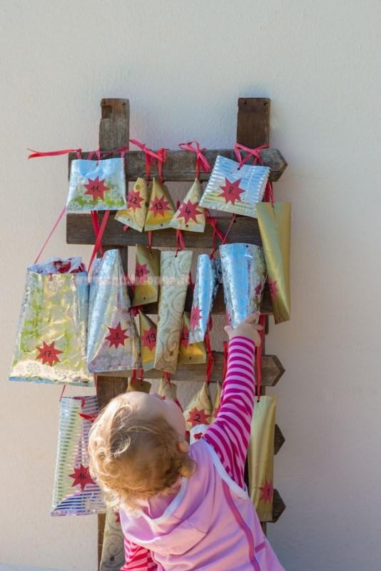 calendario dell'avvento pacchetti su scala legno bambino prende regalo