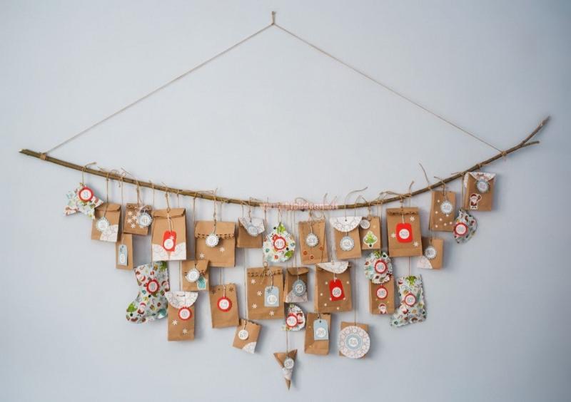 calendario dell'avvento con sacchetti appeso al muro con ramo e spago