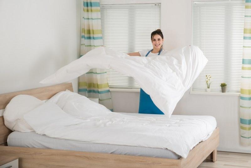 pulizia di primavera camera da letto donna rifà il letto lenzuola