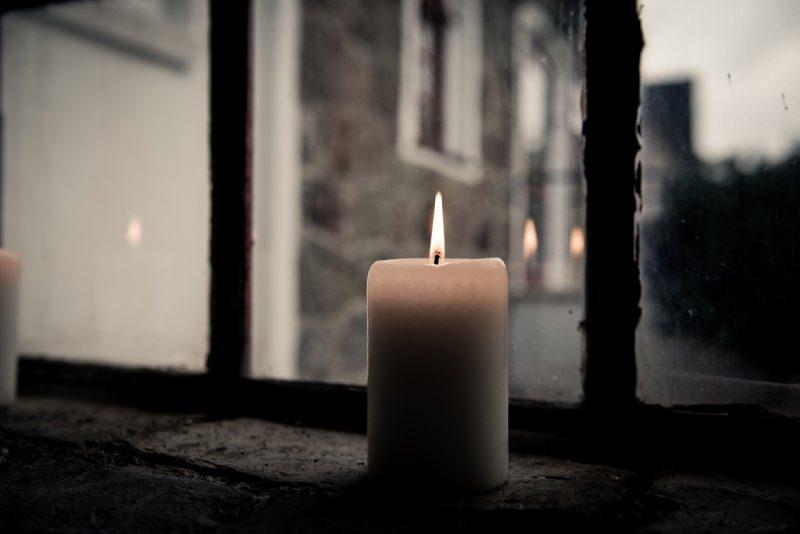 candela fiamma accesa alla finestra