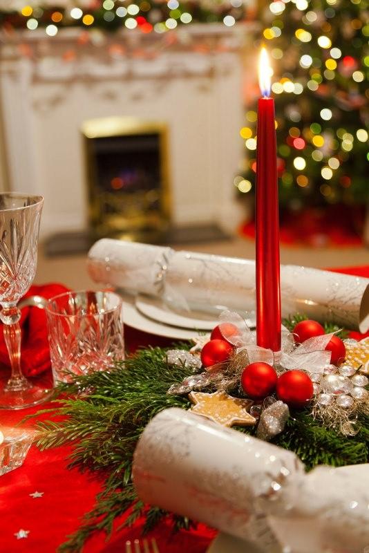 Come apparecchiare la tavola di Natale segnaposto candela rossa fiamma accesa luci albero christms cracker rami abete calici cristallo tovaglia rossa
