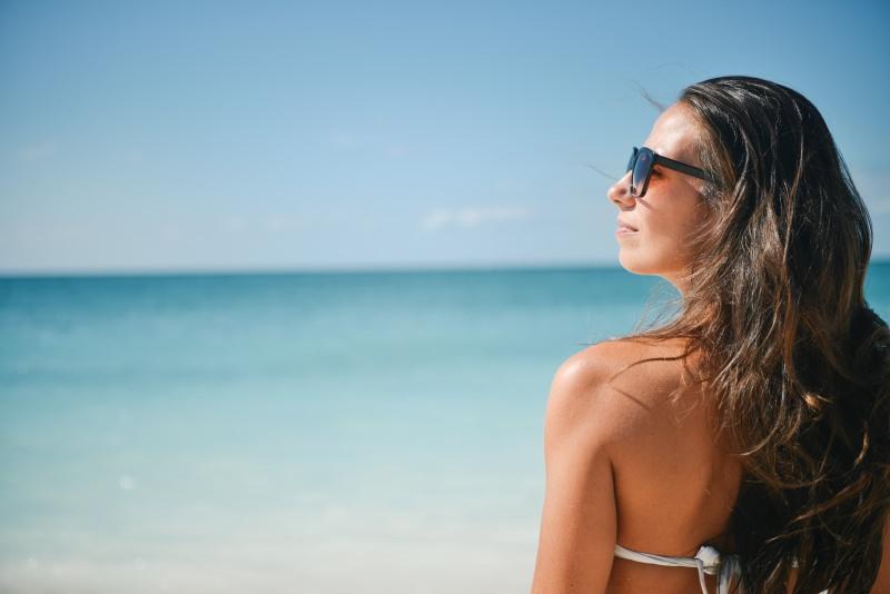 6 consigli beauty per l'estate capelli bellezza donna lunghi castani sunglasses occhiali da sole mare cielo azzurro spiaggia bikini bianco