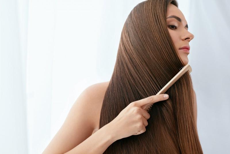 donna capelli lunghi lisci castani si pettina con pettine legno