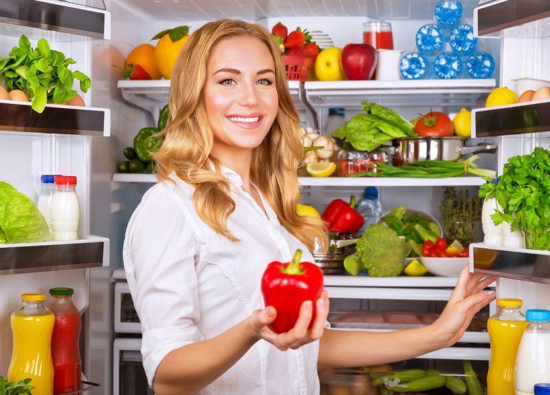 bella donna bionda prende peperone rosso dal frigo pieno di spesa frutta verdure acqua succhi