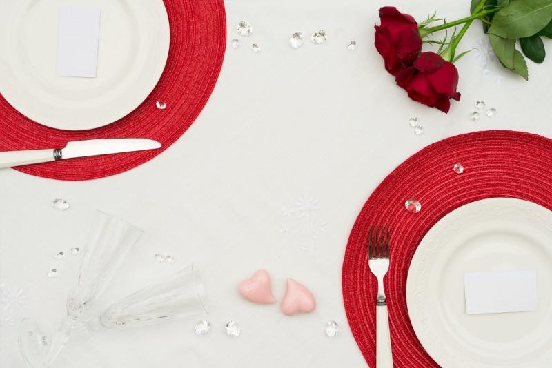tavola apparecchiata san valentino tovaglia bianca sotto piatto rosso brillanti rose rosse