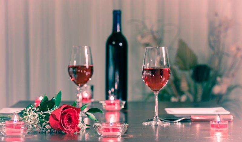 cena romantica rosa rossa tavolo apparecchiato bottiglie vino rosso tea light fiamma accesa