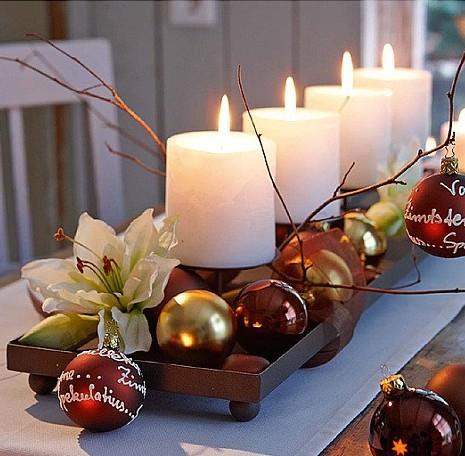 Come fare centrotavola natalizio idee originali decorazioni tavola di natale quattro candele bianche fiamma accesa base legno noce palle sfere metallo oro marrone rame bordeaux fiore giglio bianco