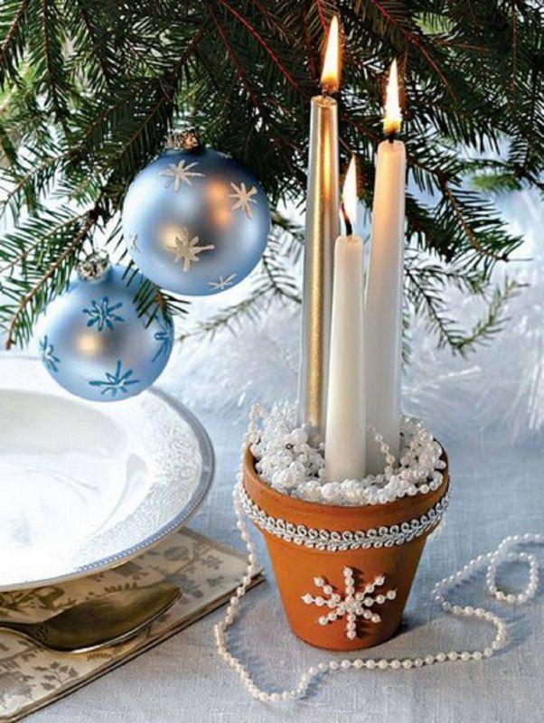 Come fare centrotavola natalizio idee originali ramo albero di natale decorazioni sfere azzurro fiocco di neve glitter tre candele bianco oro vasetto coccio decorato passamaneria bianca filo di perle cucchiaio piatto tovagliolo tovaglia azzurra
