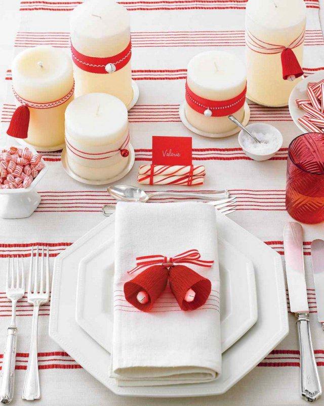 come fare centrotavola natalizio idee originali decorazioni apparecchiare tavola tovaglia bianca strisce rosse posate argento forchette piatti ottagonali porcellana bianca tovagliolo segnaposto camapane rosse nastro bianco rosso candele segnaposto nome bicchiere vetro rosso