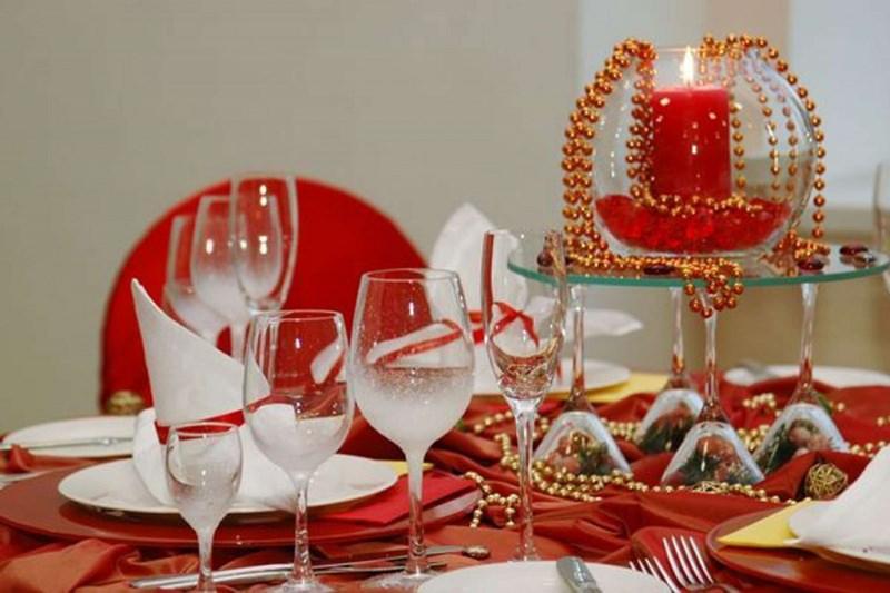 come fare centrotavola natalizio idee originali tovaglia rossa bianca calici vetro cristallo filo perle oro flûte vaso vetro candela rossa fiamma accesa