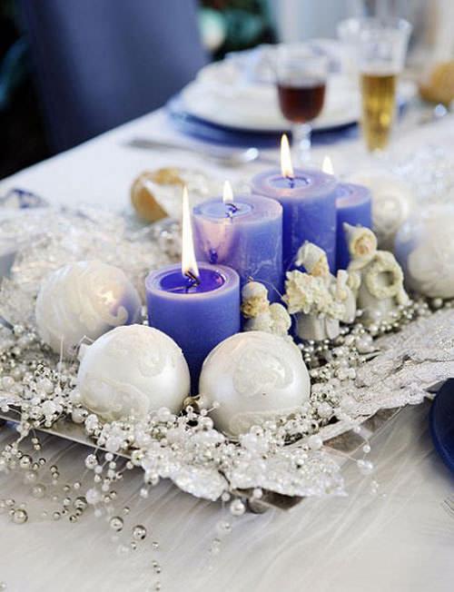 come fare centrotavola natalizio idee originali vassoio quattro candele blu avvento angeli ceramica fiamma accesa sfere palle bianche glitter filo perle foglie argento decorazione tavola panino piatti porcellana bianca sotto piatto blu calice vino rosso flûte cristallo spumante posate apparecchiata tovaglia bianca