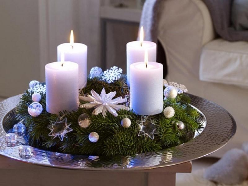 come fare centrotavola natalizio idee originali vassoio rotondo argento martellato rami verdi stelle trasparenti sfere argento fiocco di neve bianco quattro candele avvento bianche fiamma accesa