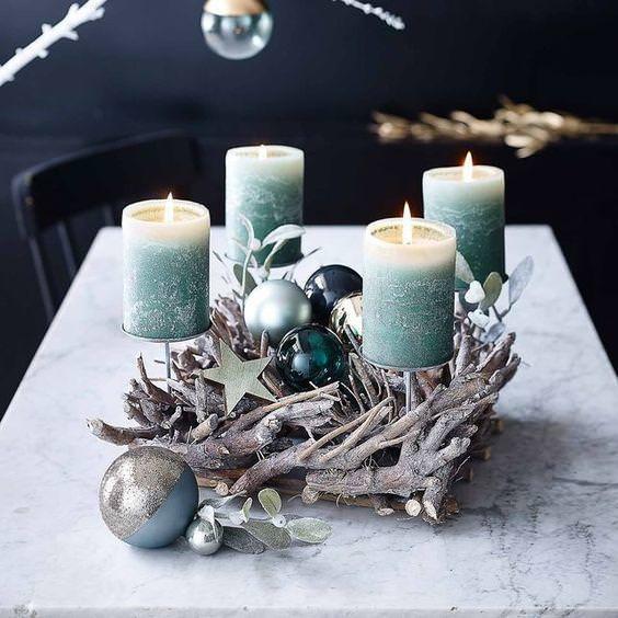 come fare centrotavola natalizio idee originali quattro candele azzurro fiamma accesa rami secchi stelle sfere argento glitter ottanio
