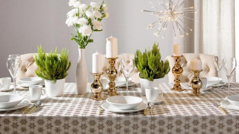 come fare centrotavola natalizio idee originali decorazione vaso fiori bianchi ceramica bianca candeliere dorato candela bianca alberello lemon cipresso calici cristallo piatti tazzine caffe porcellana bianca tovaglia decoro fiocco di neve sedie poltrone pelle bianca capitonné luci led