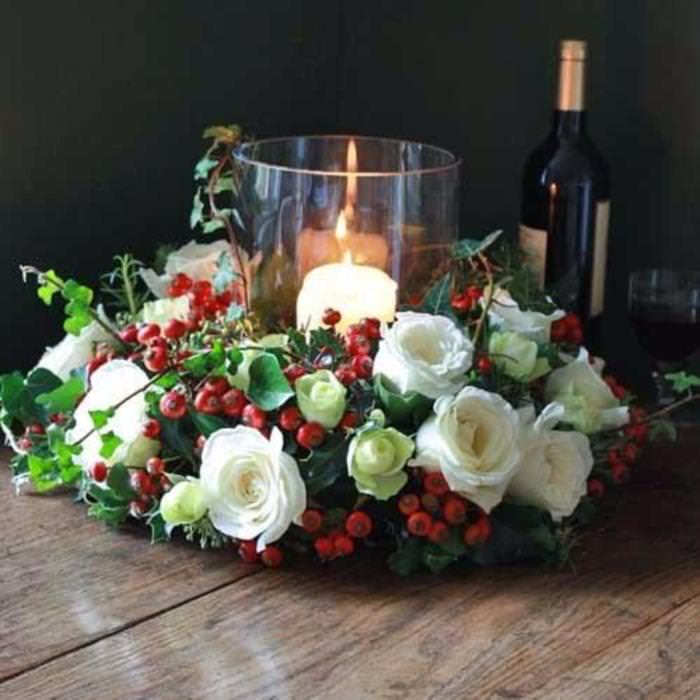 Come fare centrotavola natalizio idee originali decorazioni natalizie tavola di natale centro porta candela vetro fiamma accesa rose bianche rosa canina rossa tavolo legno bottiglia vino rosso bicchiere calice cristallo