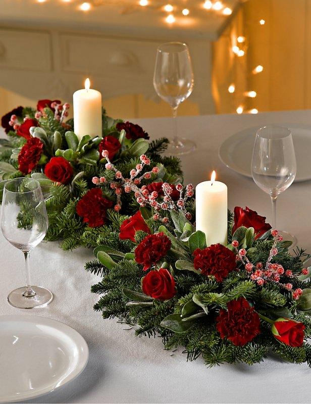 Come fare centrotavola natalizio idee originali decorazioni tavola di natale centro tavola fiori rose rosse garofano foglie verdi abete agrifoglio candele fiamma accesa piatti porcellana bianca calici cristalli luci led
