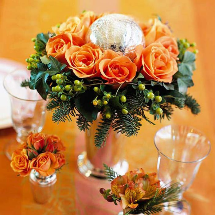 Come fare centrotavola natalizio idee originali centro tavola rose arancioni rami verdi vaso vetro bicchieri cristallo sfera argento