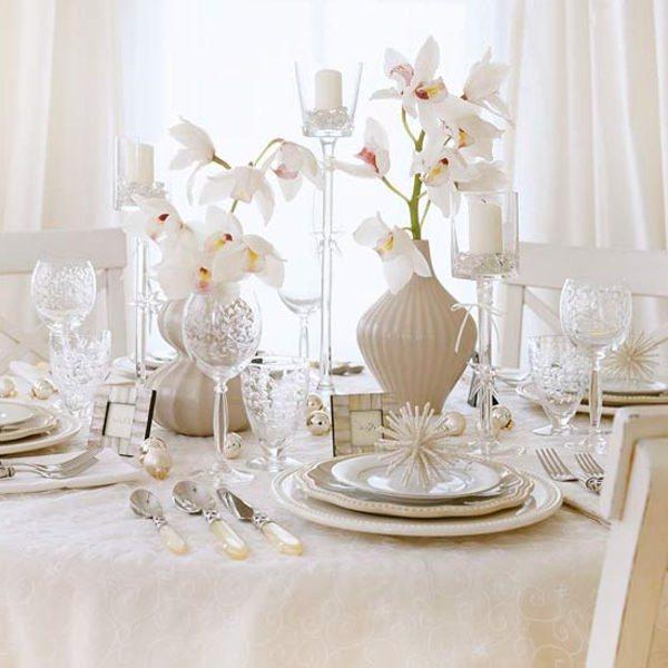 Come fare centrotavola natalizio idee originali decorazioni floreali orchidee bianche total white sfere cristalleria calici cristallo candeliere candela bianca vaso ceramica sedie tenda porta foto madreperla segnaposto posate cucchiaio coltello forchetta tovaglia sotto piatto tovalgiolo