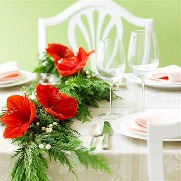 Come fare centrotavola natalizio idee originali decorazioni floreali fiori rossi foglie verdi sedie legno bianco tovaglia verde calici cristallo piatti porcellana bianca