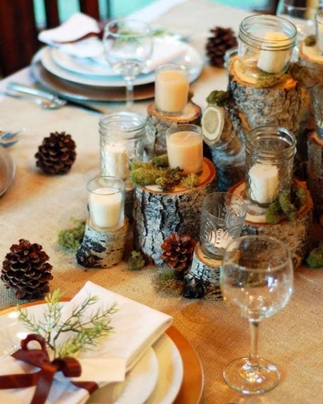 Come fare centrotavola natalizio idee originali decorazione tavola di natale apparecchiata piatti porcellana bianca cristalleria calici cristallo centro tavola ceppo legno bicchieri vetro candele bianche muschio pigna segnaposto porta tovagliolo bianco ramo verde nastro raso marrone