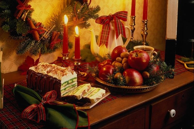 Come fare centrotavola natalizio idee originali country style vassoio frutta rossa mele, anacardi rami verdi dolce candelieri argento candele rosse fiamma accesa ghirlanda sempreverde bacche cannella teiera porcellana bianca tazza da te mobile legno noce tovagliolo verde nastro rosso