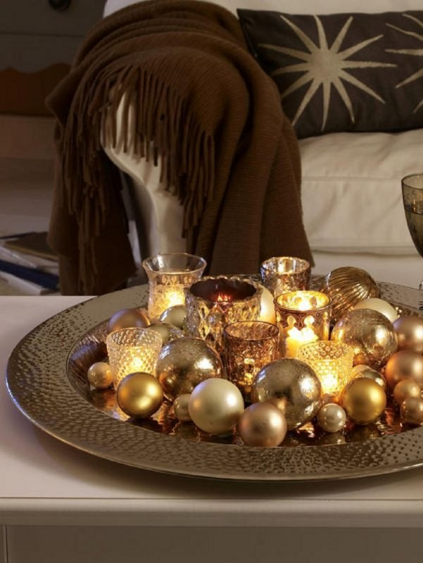 Come fare centrotavola natalizio idee originali decorazioni vassoio argento sfere dorate oro vetri dorati martellati luce tea light divano bianco cuscini sciarpa marrone frangia