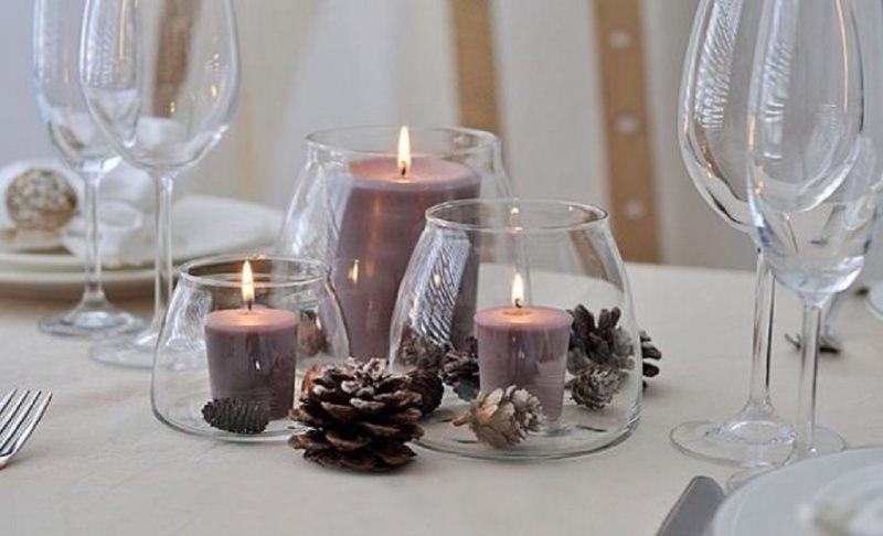 Come fare centrotavola natalizio idee originali decorazione tavolo candele viola dentro vaso vetro pigna pigne fiamma accesa calici cristallo tovaglia bianca