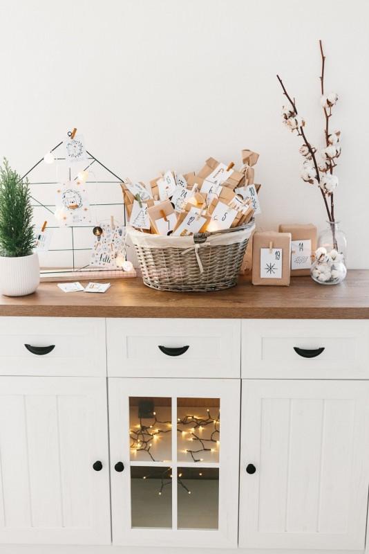 calendario dell'avvento sacchetti dentro cesta vimini sopra mobile legno bianco luci led pacchetti regalo