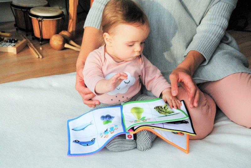 bambino piccolo legge libro stoffa mammatamburi maracas xilofolo