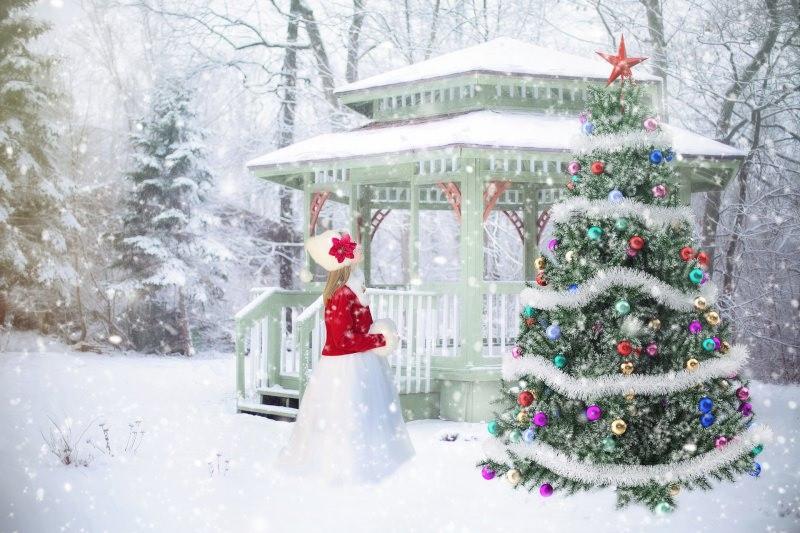 Il Natale, la malinconia e le assenze paesaggio innevato ragazza prega davanti albero luci palline neve decorazioni