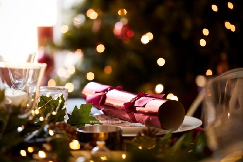 christmas cracker sulla tavola apparecchiata albero di Natale luci