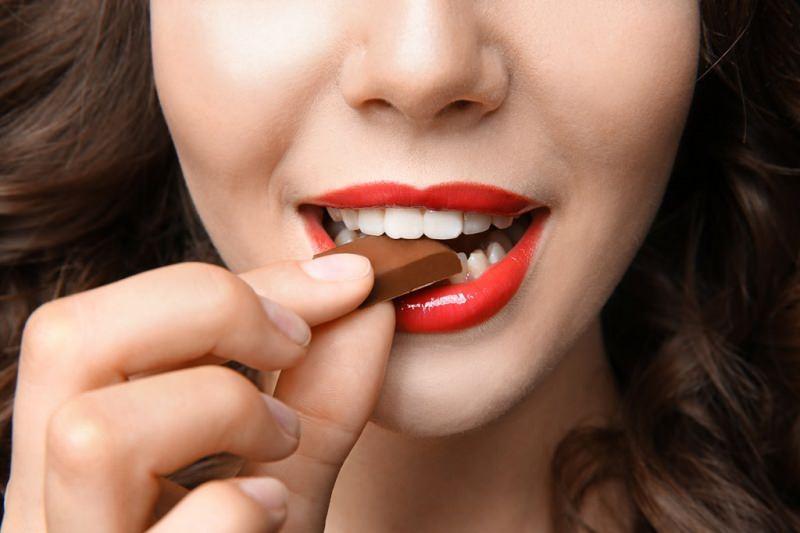 Dimagrire col cioccolato viso donna capelli castani sorriso morde quadratino cioccolato denti bianchi rossetto rosso