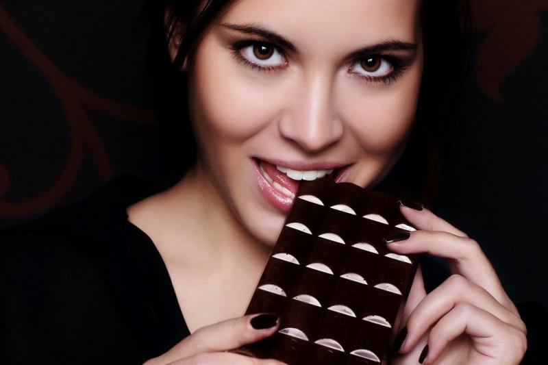 Dimagrire col cioccolato viso donna capelli castani bella morde tavoletta cioccolato denti bianchi mani unghie smalto marrone